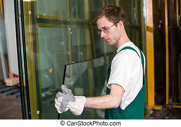 Glazier in workshop handling glass - Worker in glazier's ...