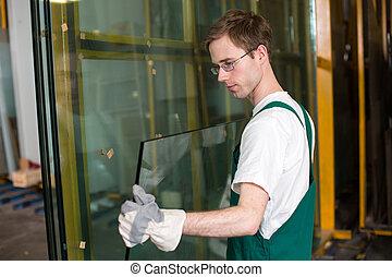Worker in glazier's workshop, warehouse or storage handling glass