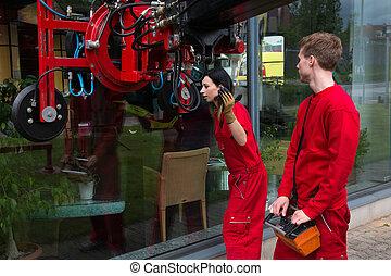 Glaziers operating a glass installation crane at glazier's workshop