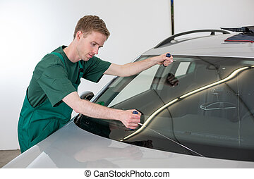 Glazier removing windshield - Glazier cutting adhesive of...
