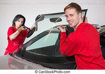Glazier replacing windshield