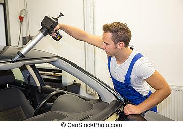 Glazier with application gun in garage replacing windshield...
