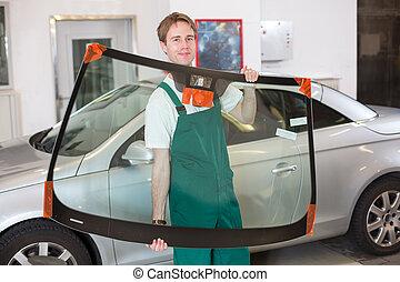 Glazier with car windshield made of glass - Glazier handling...