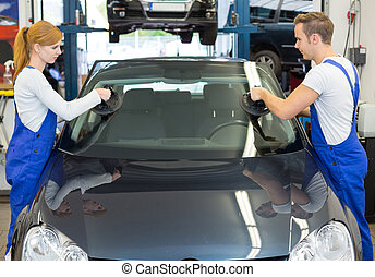 Glaziers replace windshield or windscreen on car after stone-chipping
