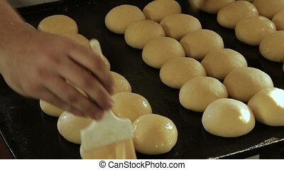Smearing buns with glaze - Glazing buns. Buns on the baking...