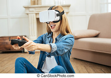 Gleeful woman wearing virtual reality glasses and using remote control