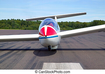 Glider at rest on a tarmac runway.