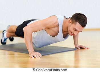 glimlachende mens, doende duw-op, in de gymnastiek