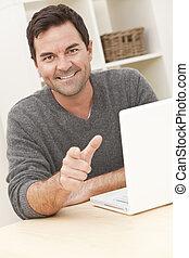 glimlachende mens, gebruikende laptop, computer, thuis, richtend aan, fototoestel