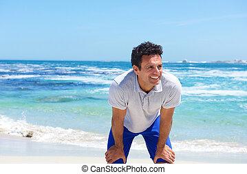 glimlachende mens, staand, met, handen op knieën, aan het strand