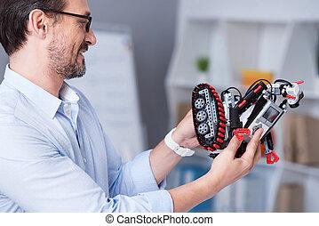 glimlachende mens, verrichtend, een, nieuw, speelgoed robot