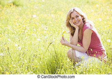 glimlachende vrouw, bloem, vasthouden, buitenshuis