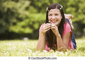 glimlachende vrouw, bloemen, het liggen, buitenshuis