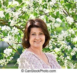 glimlachende vrouw, boompje, appel, bloeien