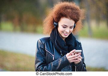 glimlachende vrouw, gebruik, smartphone, met, headphones