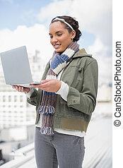 glimlachende vrouw, gebruikende laptop