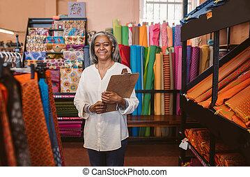 glimlachende vrouw, het houden een clipboard, in, haar, fabric winkel