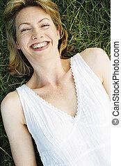 glimlachende vrouw, het liggen, buitenshuis