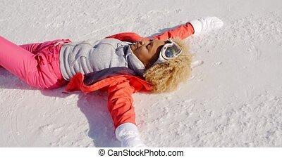 glimlachende vrouw, in, snowsuit, het leggen, op, sneeuw