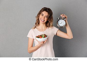 glimlachende vrouw, in, t-shirt, op, dieet, het houden bord, met, groentes