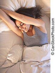 glimlachende vrouw, op bed, stretching, haar, armen
