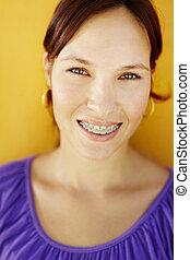 glimlachende vrouw, orthodontisch, jonge, bretels