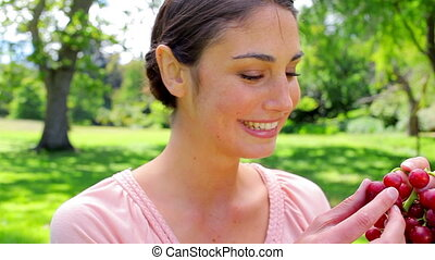 glimlachende vrouw, vasthouden, druif, fruit