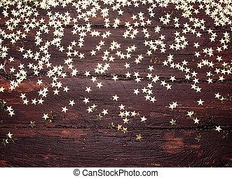 Glitter golden stars on grunge wood background. Holiday Background