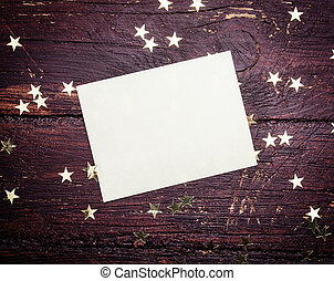 Glitter golden stars with blank paper on grunge wood...