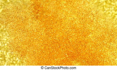 Glitter in water. Gold paint reacting in water creating...