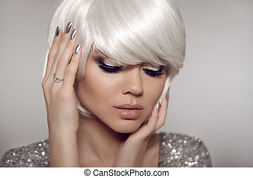 Glitter Makeup and silver manicure nails. Fashion blond with bob short hairstyle and manicured nail polish. Close up portrait of blonde girl model with white hair presenting diamond ring on finger.