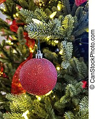 glitter red Christmas ornament hanging on branch