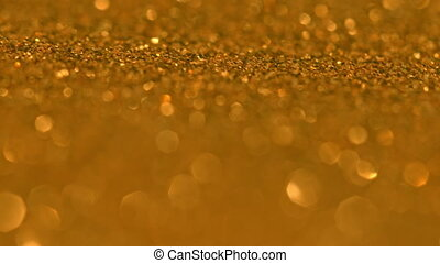 Glittering Golden Particles With Bokeh. Yellow gold defocused circular facula. Natural Floating Organic Abstract Particles. Background. Christmas and Happy new year. Slow motion.