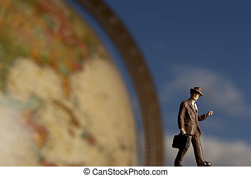 Business figurine placed with antique earth globe.