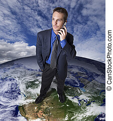 Businessman on top of earth making a cellular phone call.