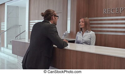 Global Business - Pan of resident talking to receptionist
