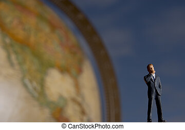 Global businessman - Business figurine placed next to globe.