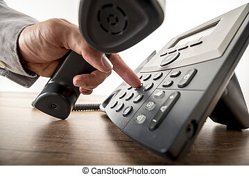 Global communication concept - closeup of male hand dialing a telephone number in order to make a phone call on a classical black landline telephone