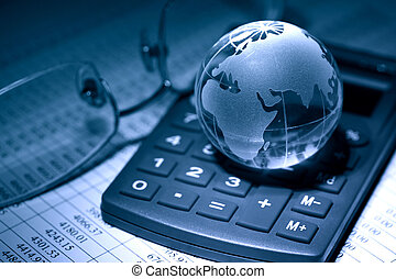 Global Economy - Business concept. Glass globe on calculator...