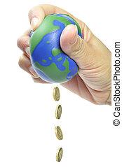 Global economy - Hand squeezing coins out of a globe