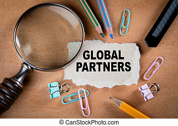 GLOBAL PARTNERS concept. Magnifying glass, stationery and note paper