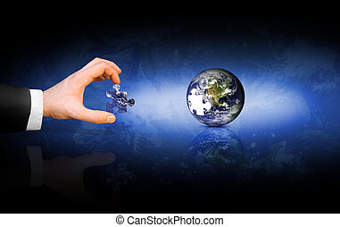 A conceptual image of a business man placing the final puzzle piece into the Earth.