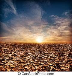 Global warming concept. Lonely drought cracked desert landscape under evening sunset sky