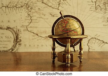 Globe against map on a wall