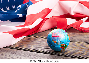 Globe and American flag on wooden background.