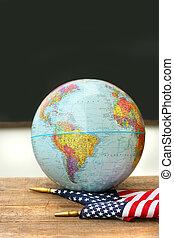 Globe and flag on school desk