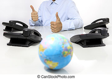 globe and like hand with office phones on desk, global international support concept