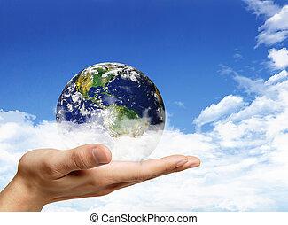 Globe in human hand against blue sky. Environmental...