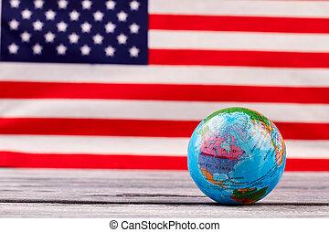 Globe on American flag background.