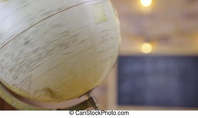 Globe on the background of an empty school class with chalkboard, close up. School, home education, distance learning. Studying in primary grades, first lesson, school knowledge. Schooling of geography in elementary school.